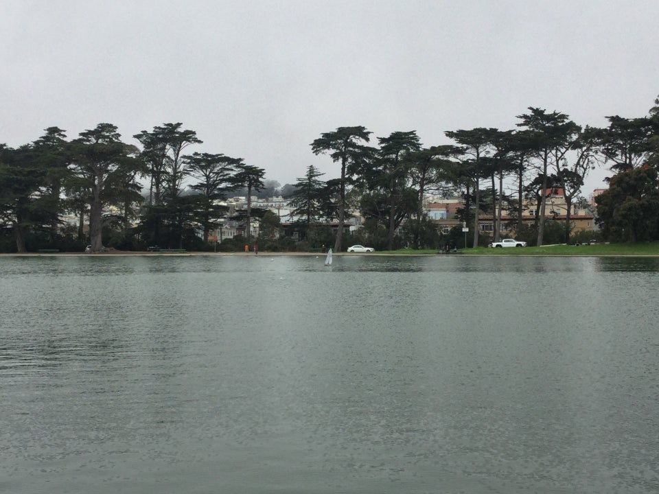 Spreckes lake with a radio-controlled model sailboat in the middle, trees on the opposite shore, under an overcast sky.