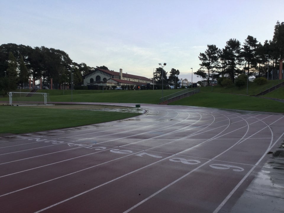 Light blue sky with clouds on the distant horizon above trees and a building on the upper edge of Kezar Stadium, as viewed from the side of the track near the starting area with track lane numbers 1 through 9 visible on the wet track, which curves toward the left, just passed a soccer goal on the field in the middle.