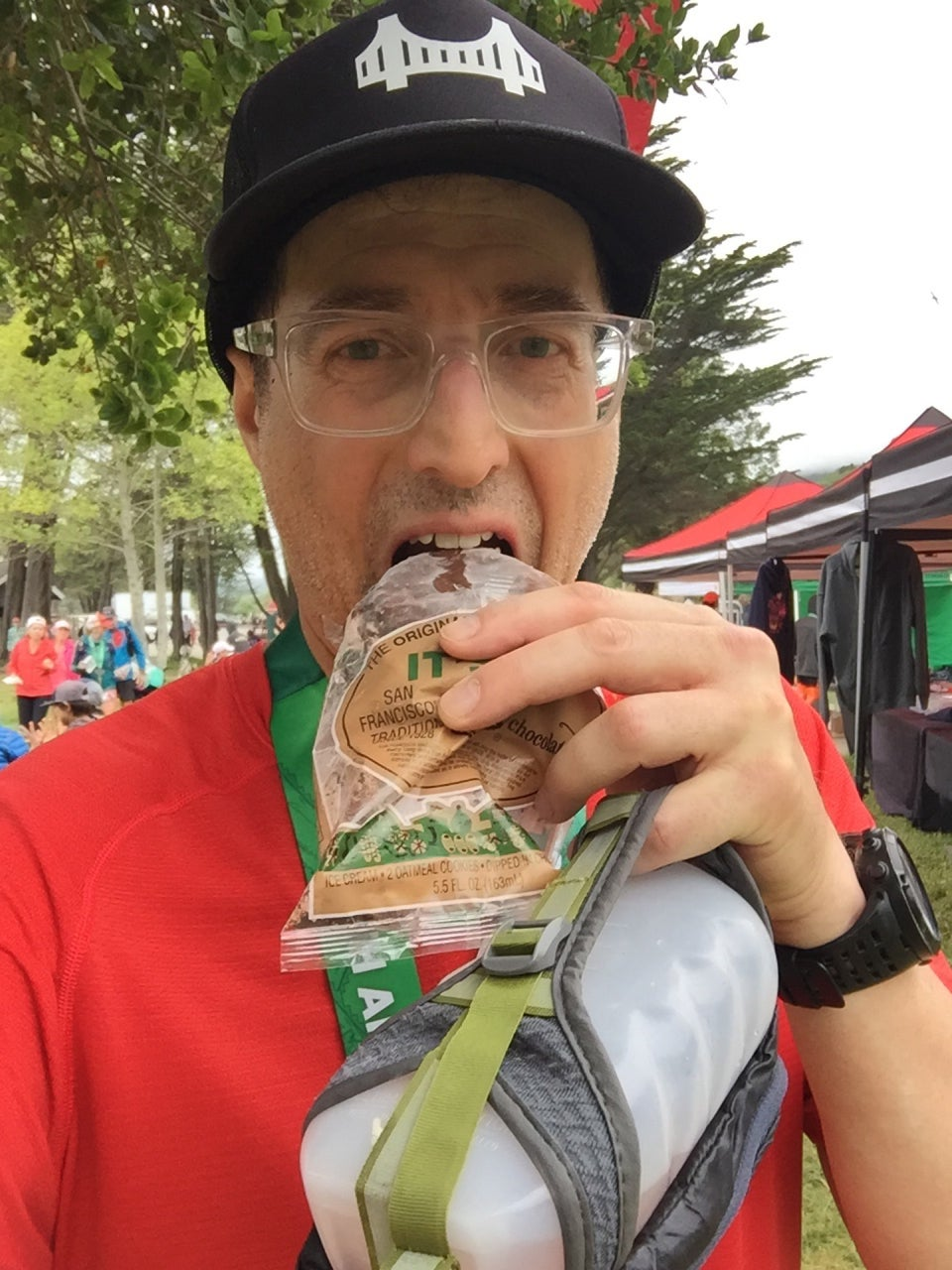 Tantek about to eat an It's It after finishing the Double Dipsea race, trees, other runners, and race tents behind him