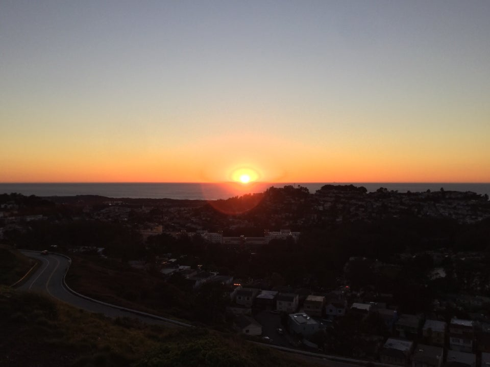 Sun half set just above the Pacific Ocean horizon, backlit dark trees on hills in the distance below, scattered houses on the hills in the shadow, a winding road nearby on the side of the hill below.