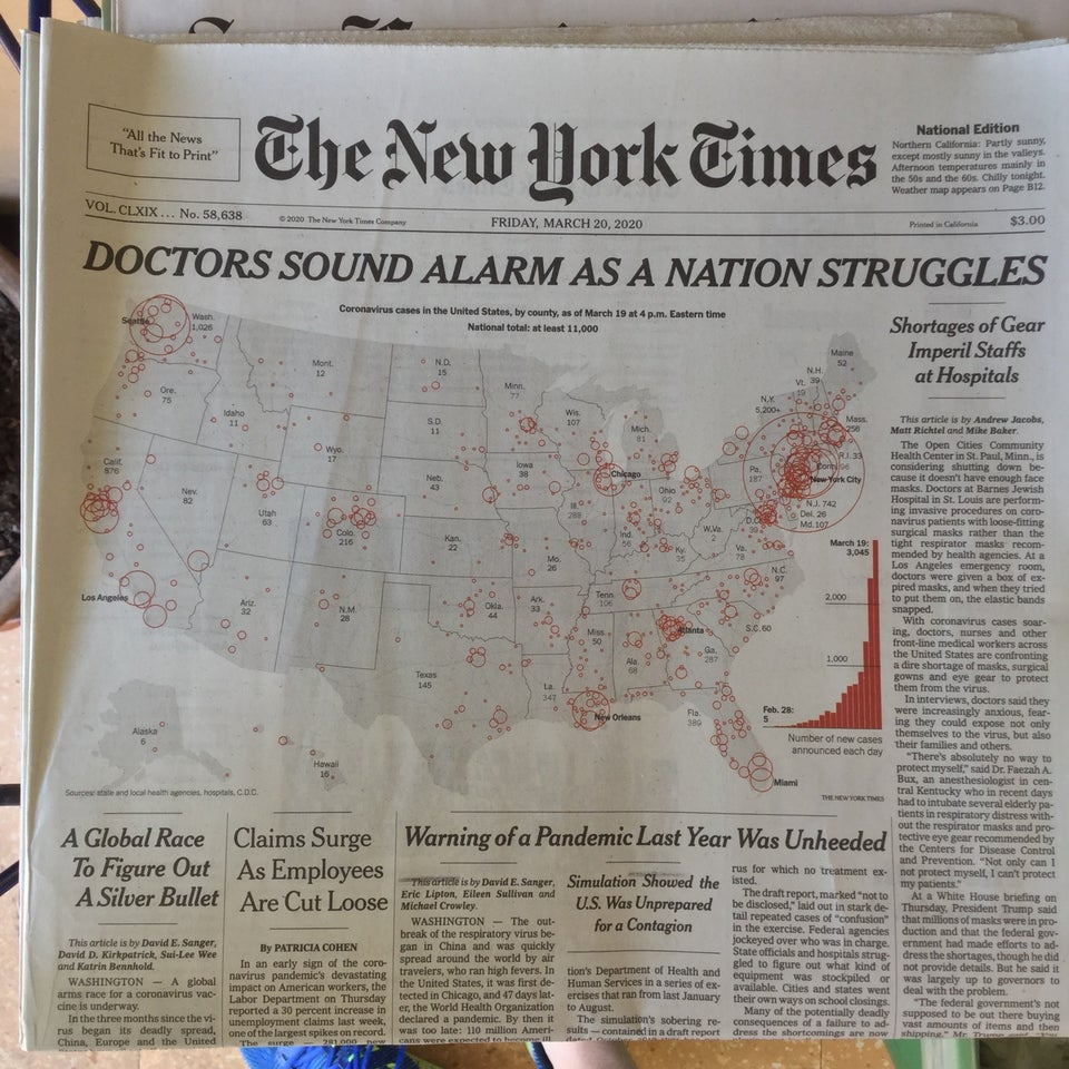 New York Times newspaper front page above the fold on March 20th, 2020 with all capitals headline DOCTORS SOUND ALARM AS A NATION STRUGGLES above a map of the United States, each state labeled with its number of cases, red circles around cities proportionate to their numbers, and a red exponentially increasing bar chart of new national cases each day from 5 on February 28th to 3,045 on March 19th.