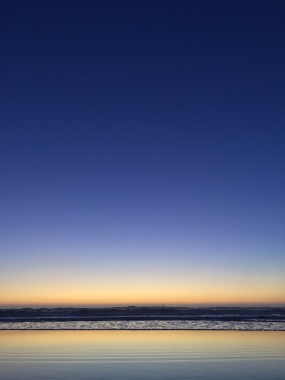 Deep blue post-sunset sky, gradient to lighter blue then yellow to an orange horizon above the ocean, crashing waves on the shore, reflecting the orange yellow blue sky above, subtle horizontal lines in the shore.