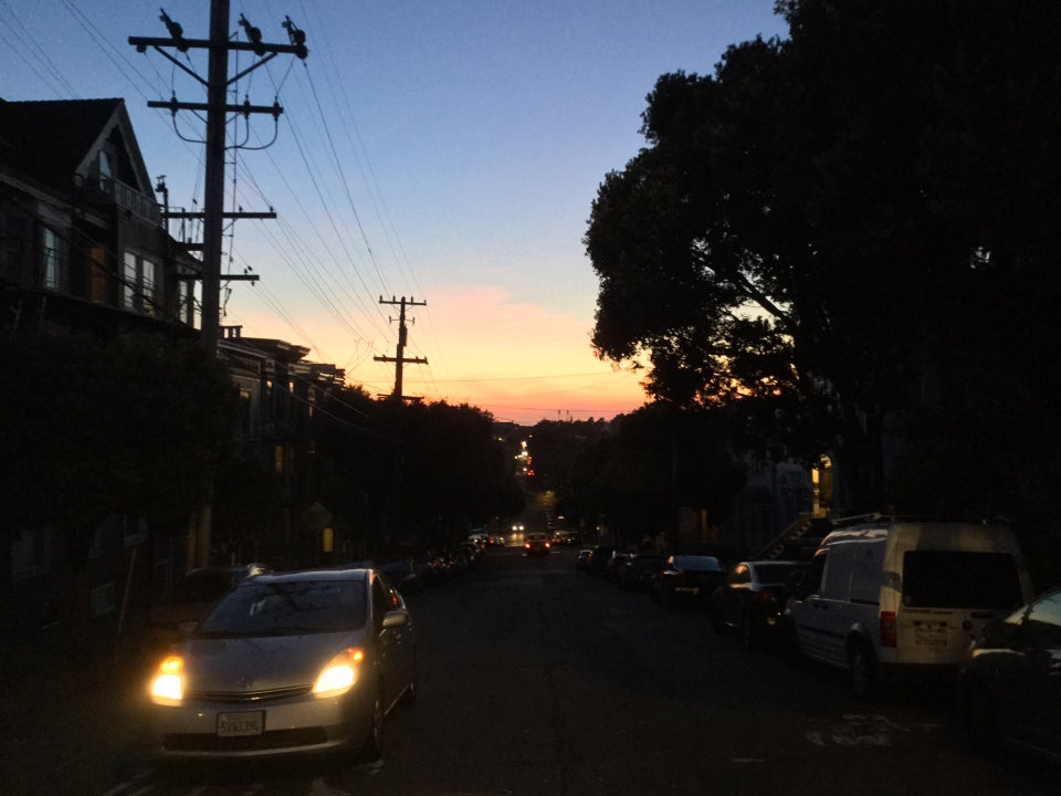 Sunset in the distance over the ocean, buildings on both sides, a car coming up an uphill street with its headlamps on.