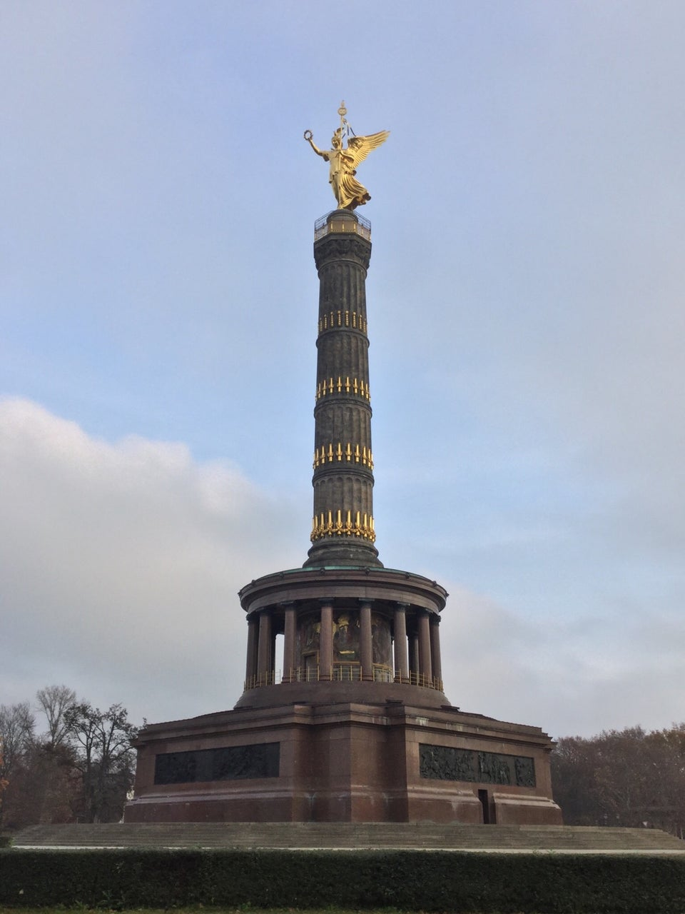 Berlin Victory Column under a partyly cloudy sky, sitting atop its base, with trees in the background on both sides.