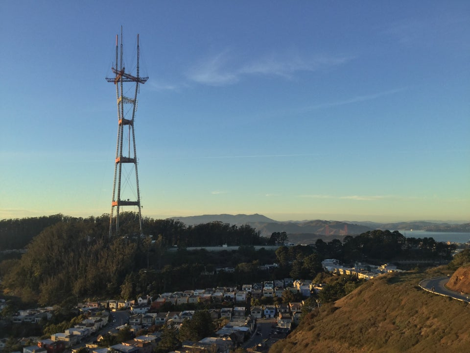 Sutro Tower nearby and a tiny Golden Gate Bridge in the distance, both lit with orange light from the sunset, blue skies with a few small cloud streaks, Mount Tam visible in the distance.