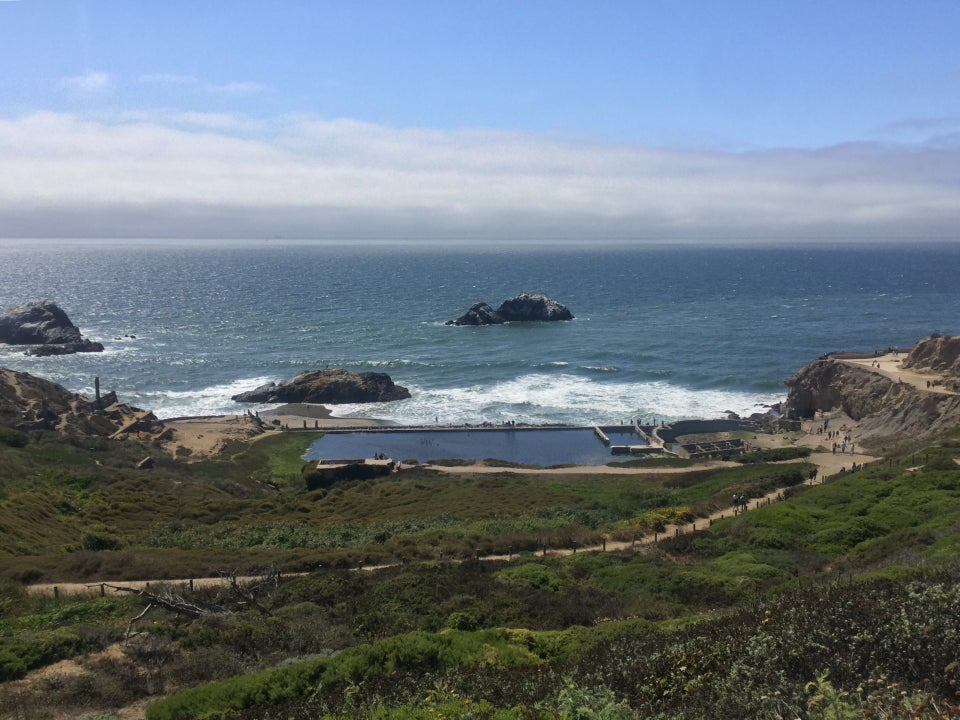Sutro baths at the Lands End Lookout with green trails in the foreground, and a blue Pacific Ocean in the background, fog gathering in the distance.