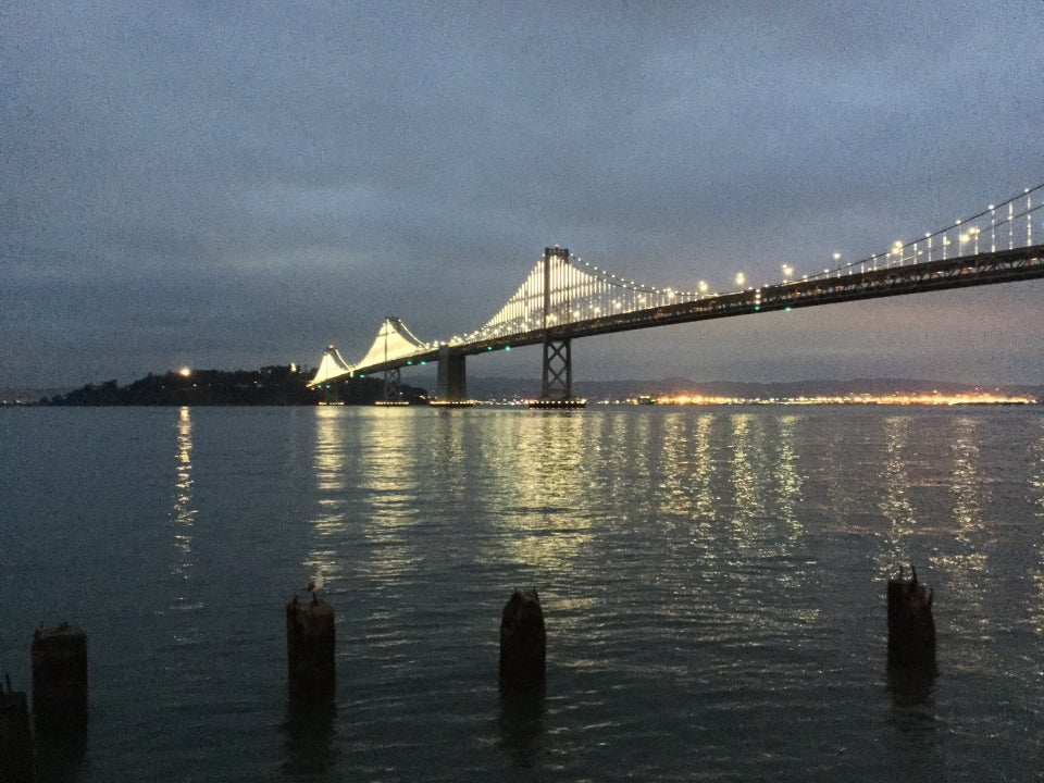 Overcast sky before dawn, the Bay Bridge still lit with its lights, reflecting on the bay below, into Treasure Island, a few dark posts from a long gone pier in the foreground.