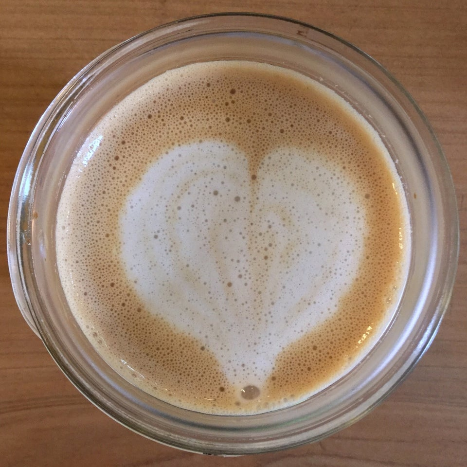 Cream colored heart on a lightly foamed latte in a glass mason jar sitting atop a woodgrain table.