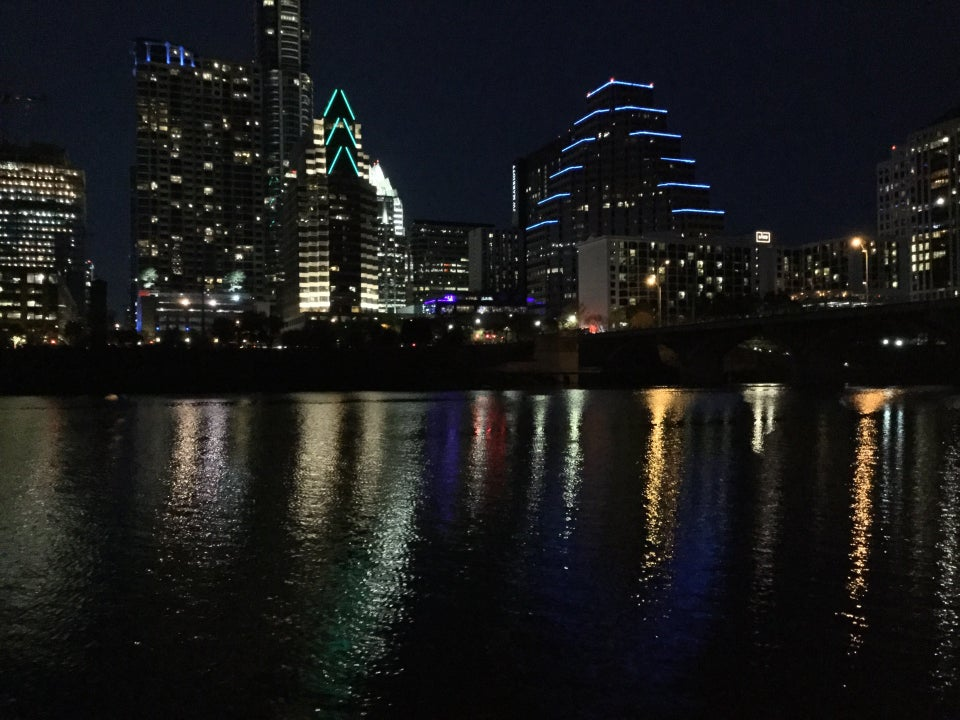 Downtown Austin skyline at night, building lights reflected in Lady Bird Lake / River in the dark.