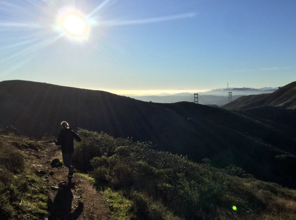 Emily runnin on Alta Trail, bright sun overhead in a clear sky, Marin Headlands in front of us, the tops of the Golden Gate bridge towers peeking up behind them, a tiny Sutro tower in the distance.