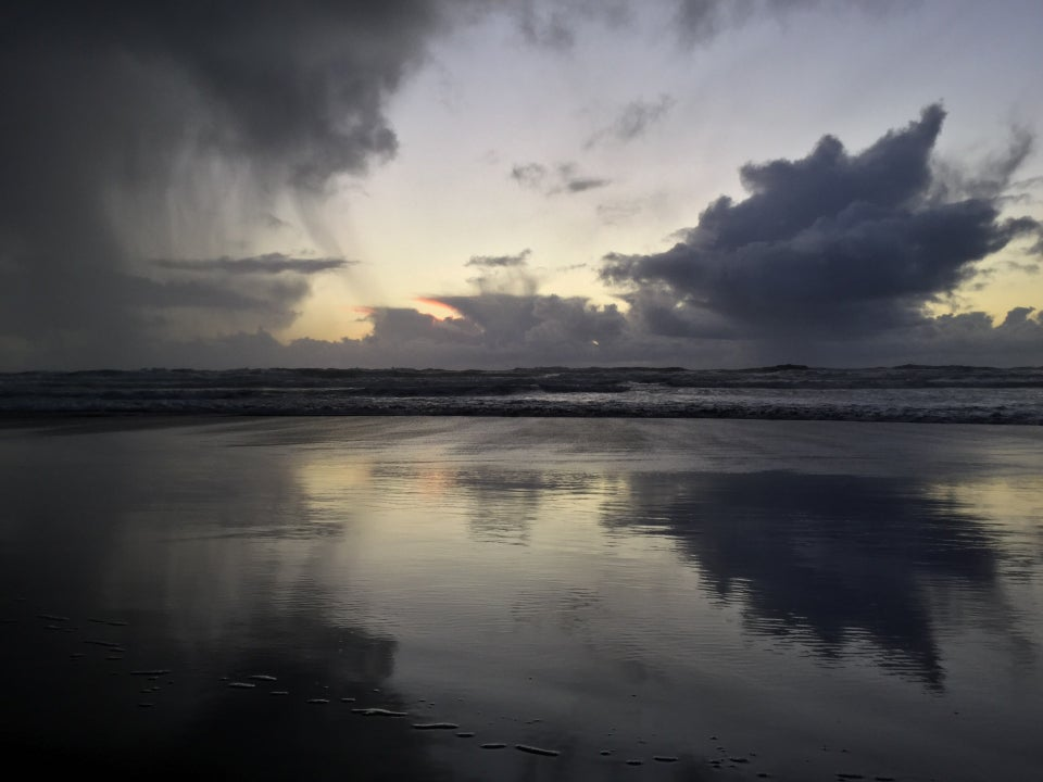 Dramatic storm cloud shedding some rain, distant open twilight sky with clouds lined with an orange tinge from the distant sunset, nearer spiky cloud dark underneath, all reflected by the wet smooth sand in front of Ocean Beach waves.