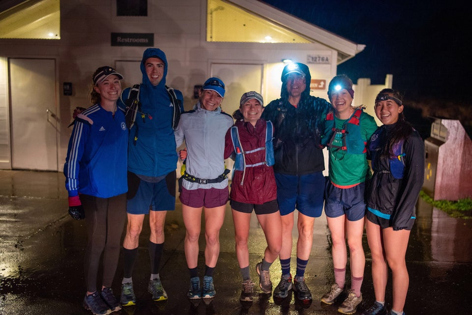 Seven runners lined up with rain gear and all but one in shorts in front of the Rodeo Beach bathrooms in the dark.