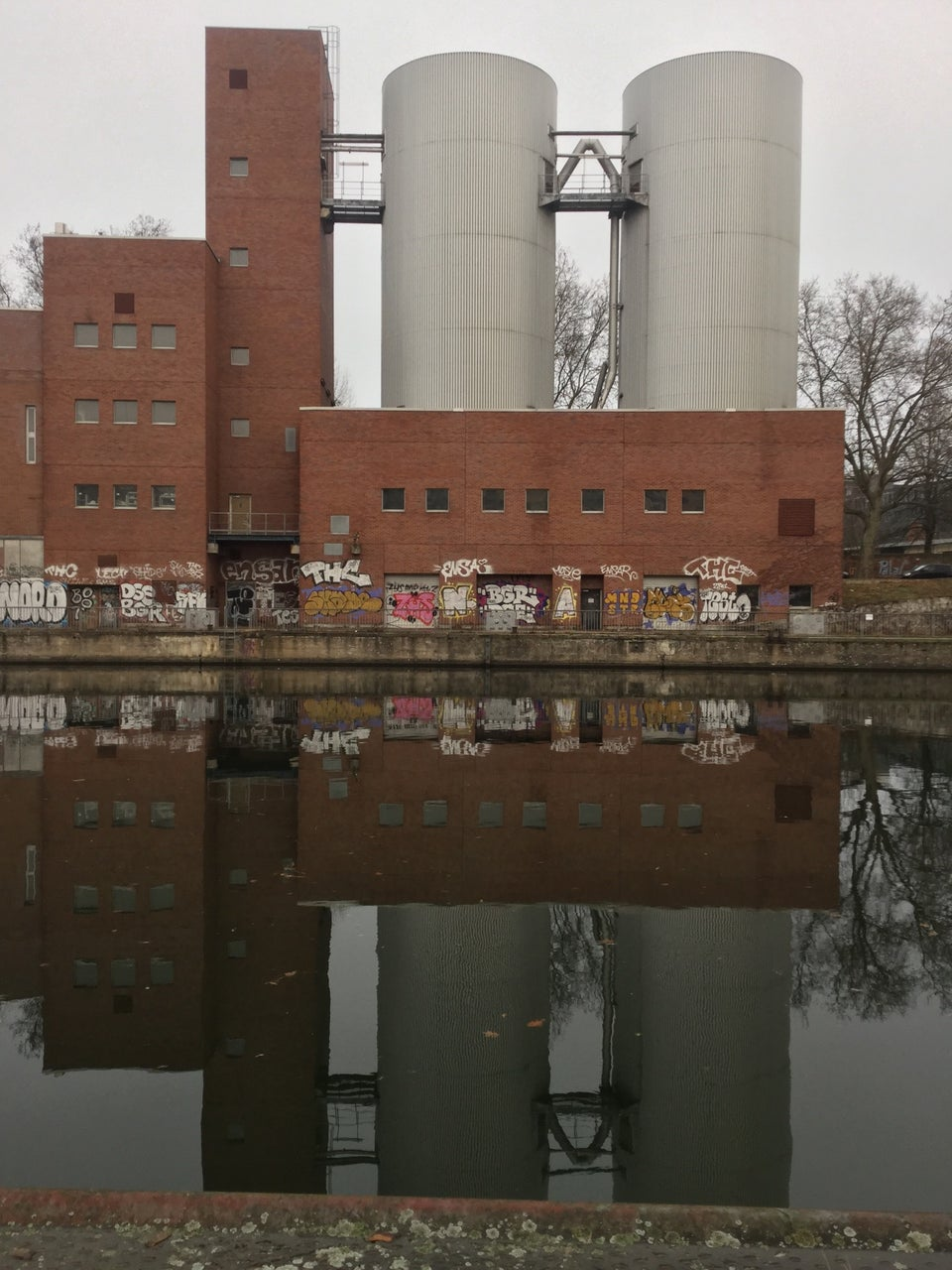 Industrial looking buildings including a couple of silos, under an overcast sky, with the river Spree in front of them reflecting the buildings, the nearby shore barely visible at the bottom.