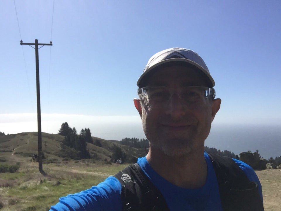 Tantek in front of the telephone pole on top of Cardiac Hill, clear blue sky above him, and a low hanging clouds behind him, just a light haze over the Pacific Ocean, sparsely grassy hills with a few trees behind him.