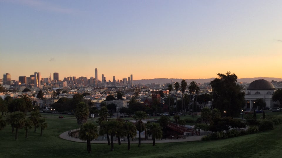 San Francisco skyline and East Bay hills bathed in sunrise on the horizon, Dolores park spanning the foreground with palm trees, and walking paths curving through the lawn.