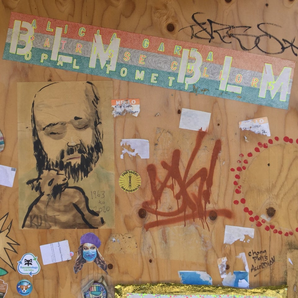 White BLM repeatedly stenciled on multicolor background segment on plywood decorated with additional art.