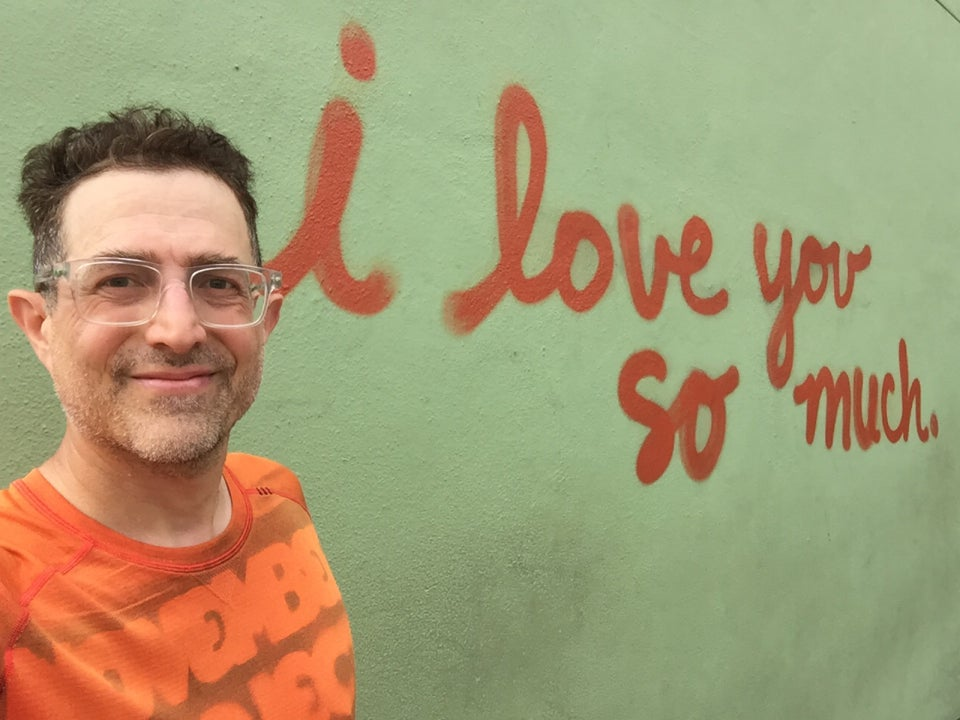 "Tantek taking a selfie standing next to red cursive graffiti writing ""i love you so much"" on a light green wall."