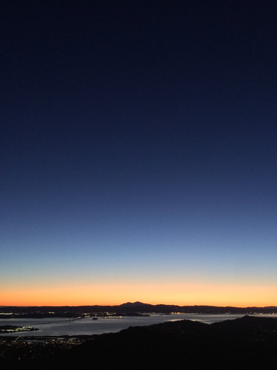 Dark blue to light blue gradient clear sky above a bright orange pre-dawn horizon backlighting the double peaked Mount Diablo and East Bay hills, city lights visible on both sides of the bay, a tiny Richmond bridge on the lower left, dark hills in the lower foreground.