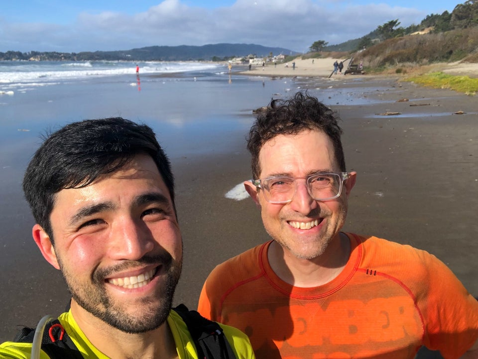 Bryan and Tantek smiling with their faces lit up by the sun, Stinson Beach behind them with a wet sandy shore, waves breaking in the distance, and hills & mountains in the far distance on the horizon.