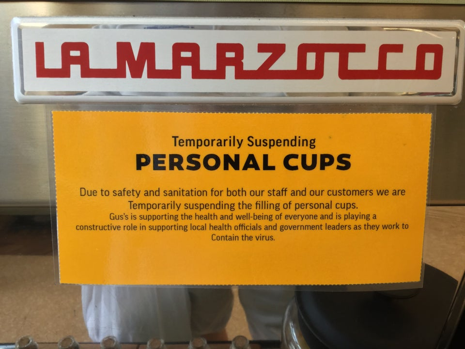 Orange printed sign stating Temporarily Suspending Personal Cups on the front of an espresso machine.