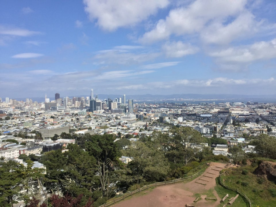 Midday view from the top of Corona Heights Park of downtown San Francisco on a sunny day, scattered white clouds on a blue sky, clear views of East Bay hills, downtown Oakland, the bay, and trees & dirt paths of Corona Heights Park below.