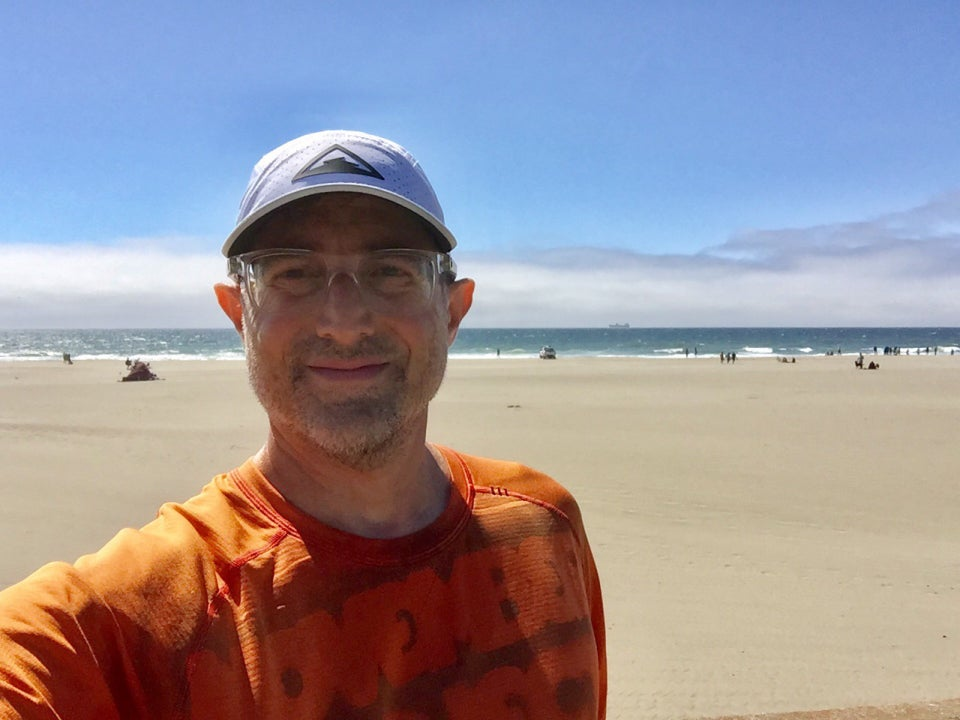 Tantek wearing a white cap and orange shirt with Ocean Beach and the Pacific Ocean behind him on a sunny day.