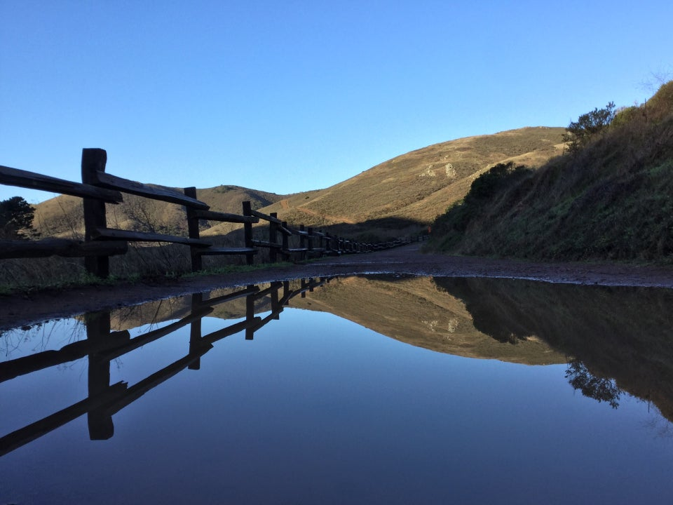 Tennessee Valley trail, large pool on the trail in the lower half reflecting the fence on the left, hills in the distance, bushes on the right, and clear blue sky above.