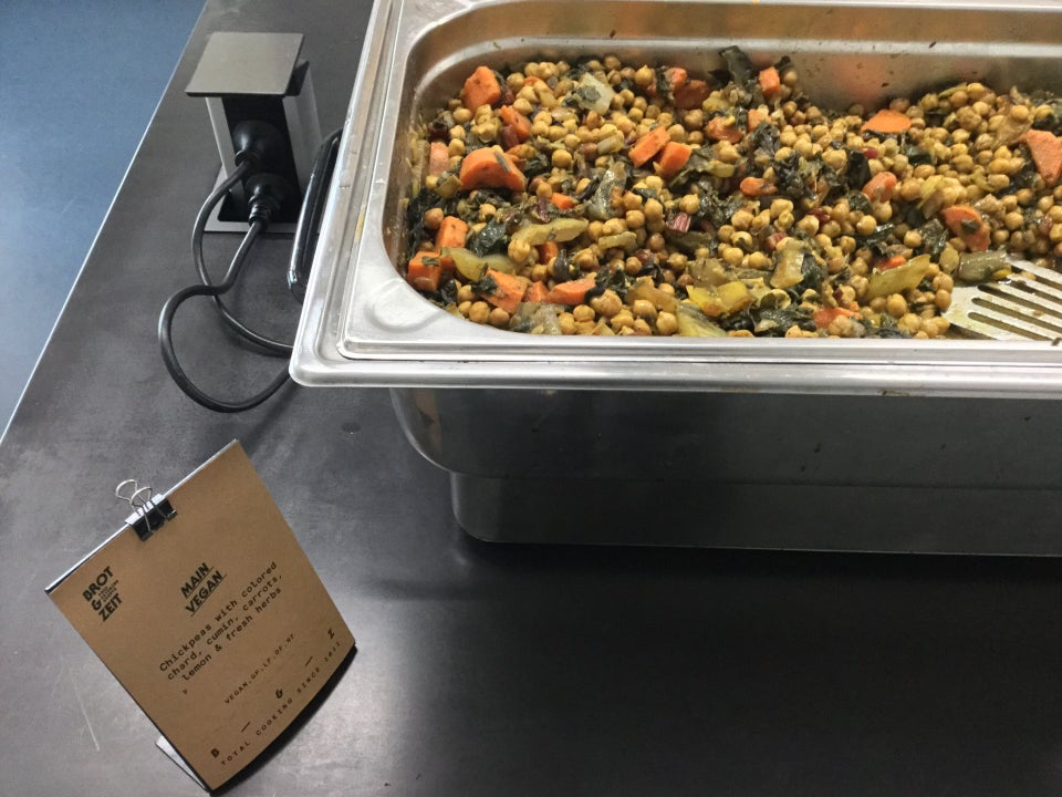 Vegan catered food: chickpeas with colored chard and other vegetables in a large metal container, being heated electrically, on a black table, with a blue floor below.