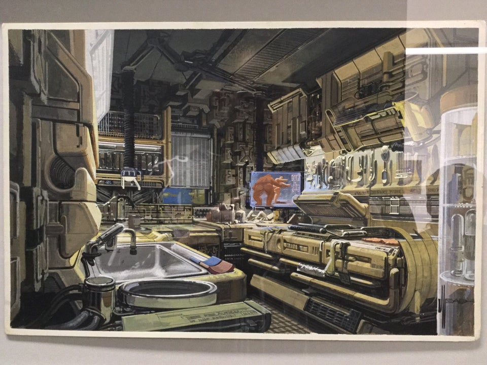 Photorealistic painting of the inside of a future urban kitchen, with highly stylized spaceship-style cabinets above, counters around the edge of the room, a window, an entertainment display, a sink, press oven, various utensils hanging from the wall.