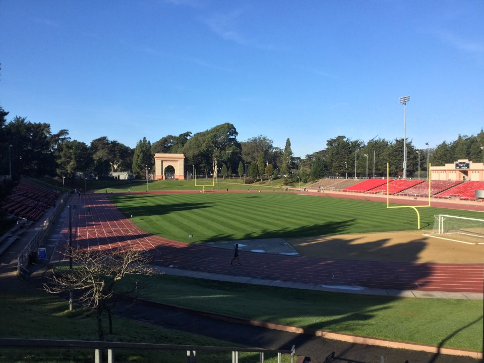 View of Kezar Stadium from the entrance, clear blue sky above, dry track below with very few runners.