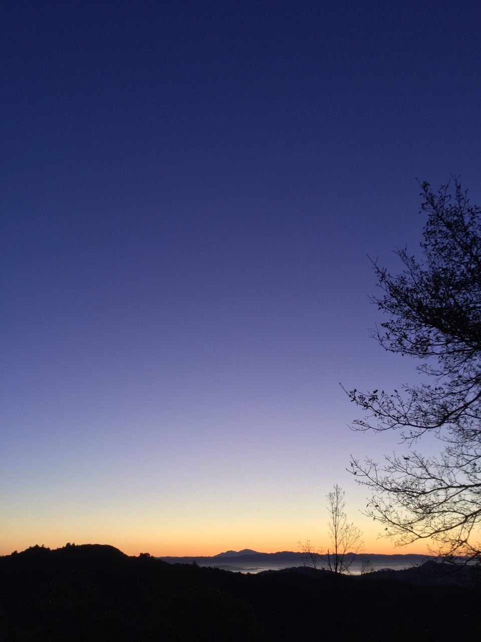 Deep blue sky with a gradient to a light purple above a yellow orange horizon with Mount Diablo in the distance, a sliver of a barely lit bay, dark outline of nearby hills.