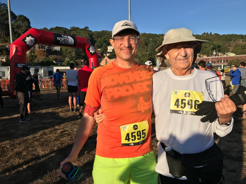 Tantek and Hasan in the morning sun in front of The North Face Endurance Challenge starting arch on a sports field in Marin City, with a forested area in the distance under a clear blue sky.