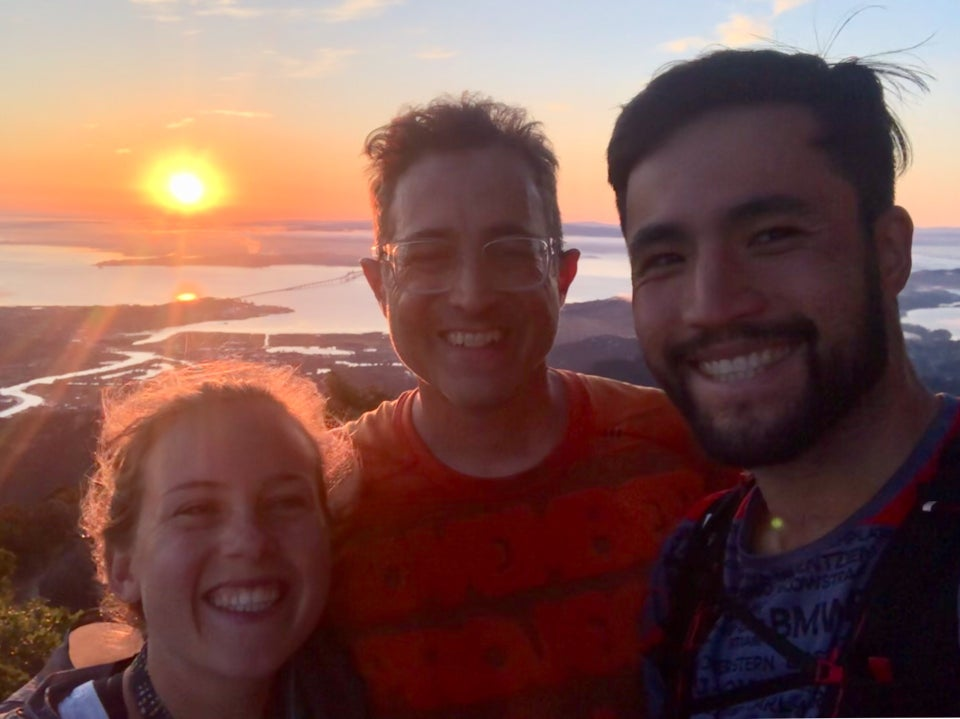 Kat, Tantek, and Bryan at the top of Mt. Tam with the sun rising just about the bay in the background, sun beams and an orange glow backlighting their hair and faces.