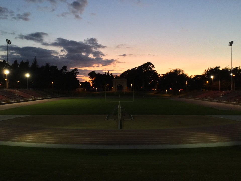 Just after sunset at Kezar stadium,mostly clear sky with gradients from light blue to orange and yellow, above dark backlist trees, the few minor stadium lights lighting up parts of the track and a bit of the center lawn, looking down the field from one field goal to the other with the orange sky in the background.