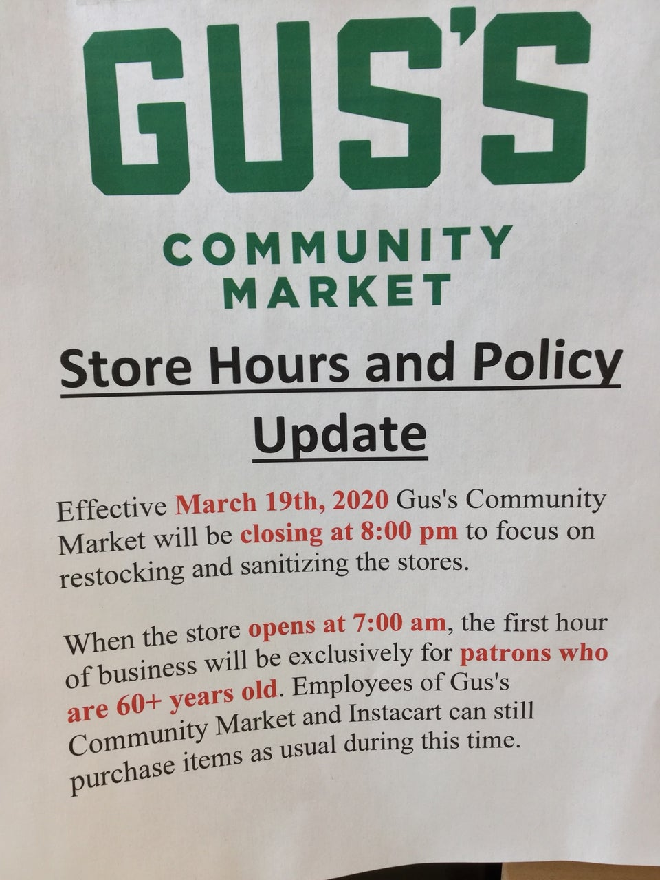 Sign at Gus's Community Market noting Store Hours and Policy Update effective March 19th, 2020, closing earlier at 8pm for sanitizing, and first hour at 7am exclusively for 60+ years old patrons, and Instacart.