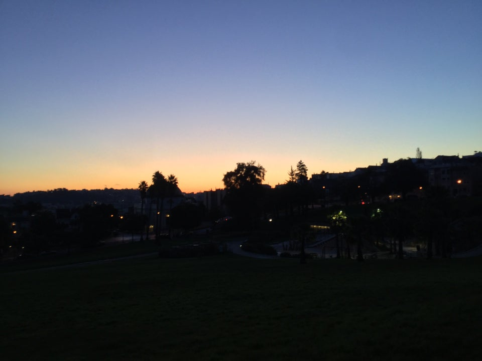 Medium blue clear sky above an orange band at the horizon, backlighting trees above Dolores Park still in darkness, yet just light enough to see a dark green tint of the grassy field.