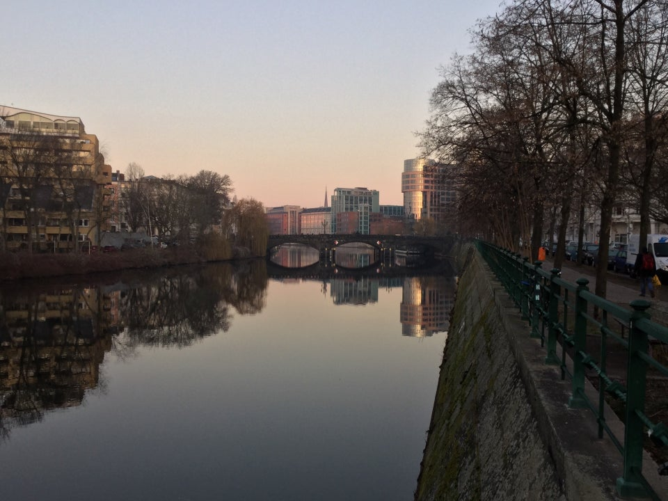 Clear sky with a slight orange glow towards the middle of the horizon, above buildings on both sides, trees on the right side of the river Spree which is showing their reflections.