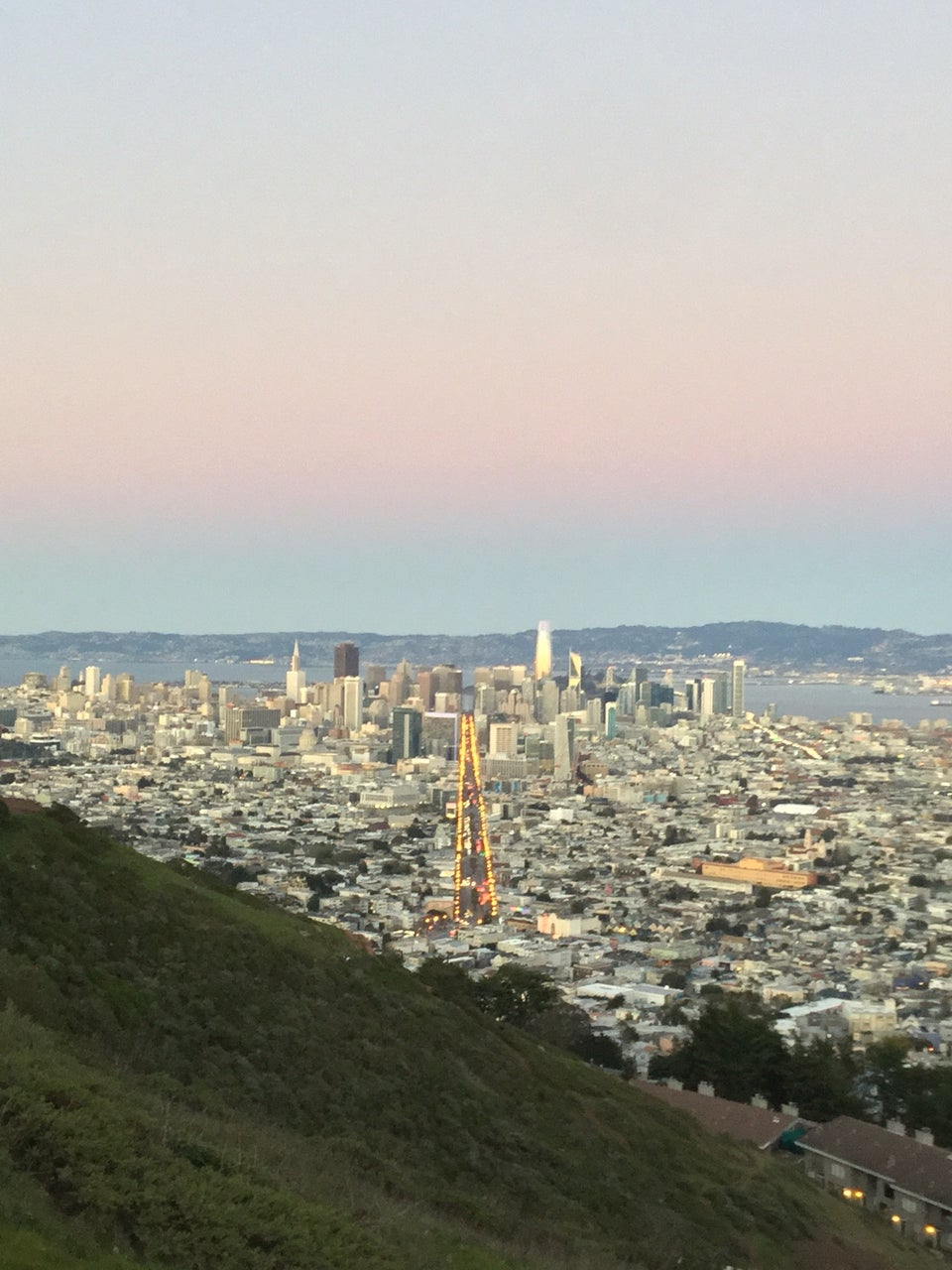 Clear gradient of white to yellow, orange, pink, purple, and blue sky above East Bay hills in the distance behind the San Francisco skyline, buildings spreading outward on either side of Market street lined with lit street lamps, nearby green hillside in the foreground.