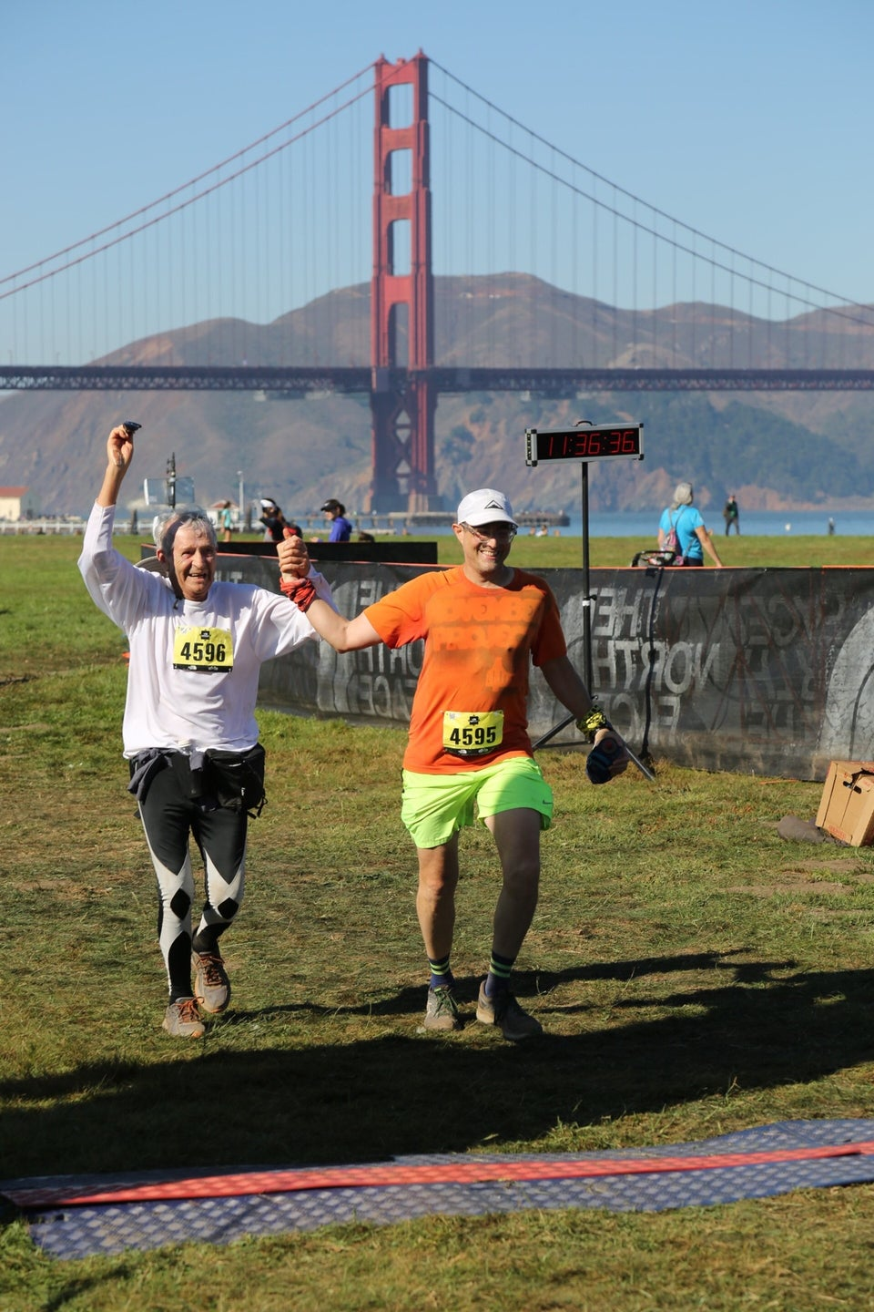 Hasan and Tantek side by side holding raised hands between them, smiling and about to cross The North Face Endurance Challenge finish line in Crissy Field, San Francisco, with the Golden Gate Bridge and Marin Headlands in the background under a clear blue sky.