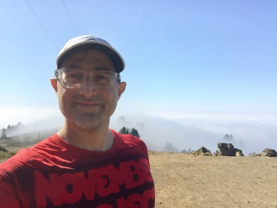 Tantek taking a selfie at the top of Cardiac hill, southern view behind him of clear blue skies above tree tops partially hidden by the thick clouds and fog below.