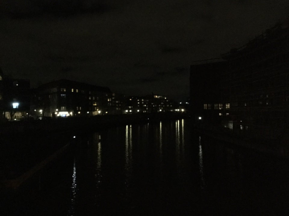 Buildings with only a few lights across the photo, reflections of the lights drawn out in the dark canal below, viewed from a bridge.