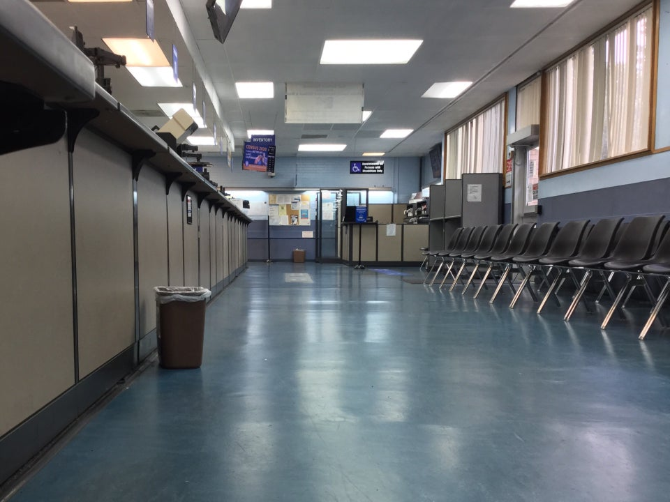 Indoors, no lines at the counters, empty seats in a waiting area to the right, signs above indicating which counter and line to go to for what.