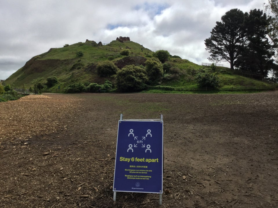Stay 6 feet apart sign in the dirt field at the base of Corona Heights Park, the hill in the middle green from recent rains, bits of blue sky peaking through white clouds overhead.