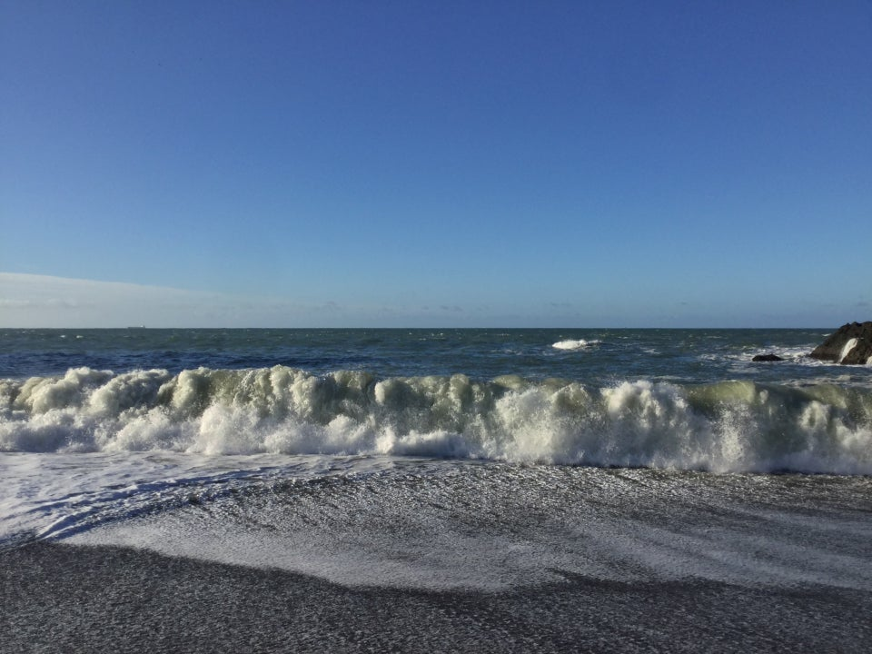 Whitecaps and crashing waves under a blue sky at Tennessee Valley beach.