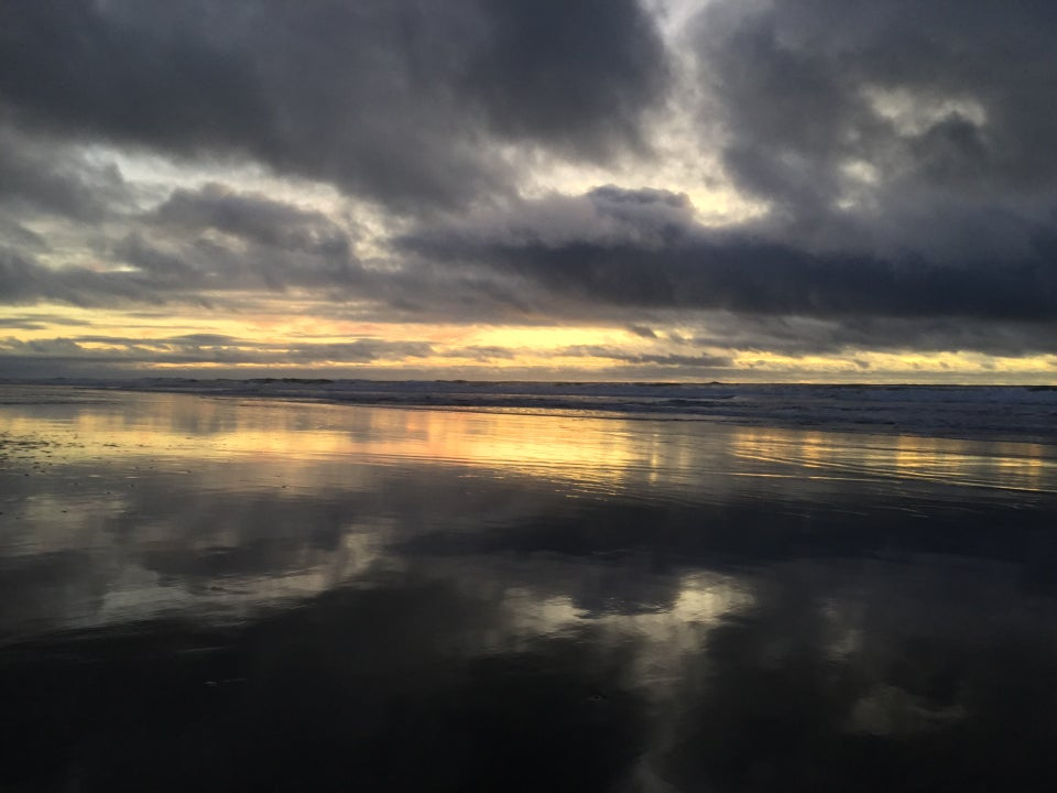 Dark clouds with wisps of sky barely visible between them, one of them making a tilted V, over a yellow orange horizon from the recent sunset behind the Pacific Ocean, waves crashing, leaving a smooth wet sandy shore with a mirror image reflection of the bright horizon, and a negative space letter T from the reflected wisps of sky surrounded by dark clouds