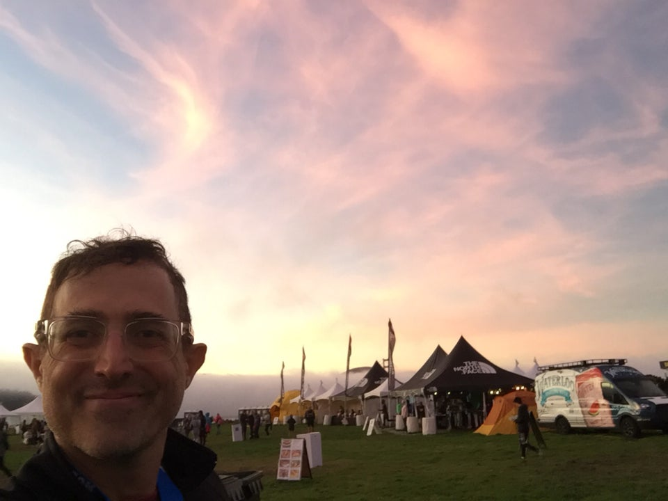 Tantek at the North Face Endurance Challenge finish area in Crissy Field in front of cotton candy colored wisps of sunset pink and orange sky, North Face expo tents behind him and to his left.