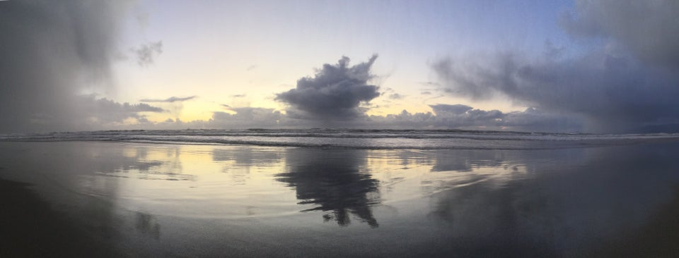Panoramic view of storm clouds to the South, an opening of nearly clear sky with clouds on the horizon and one big cloud nearer, and more storm clouds to the North above the Pacific Ocean at Ocean Beach with waves crashing and leaving behind a wet reflection on the sand of the same clouds but darker and textured with ripples as the water recedes back to the ocean.