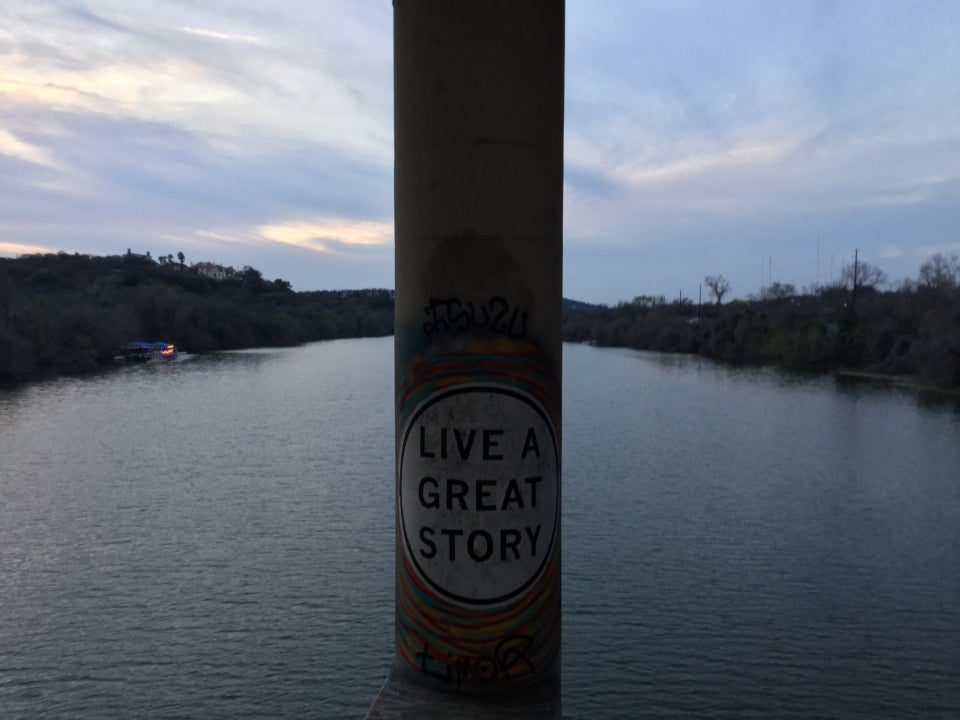 View from a bridge of Lady Bird Lake, with a cement column in front of us dividing the view, with a large white circle painted on it with the all capitals words LIVE A GREAT STORY written inside in a large sans-serif font.