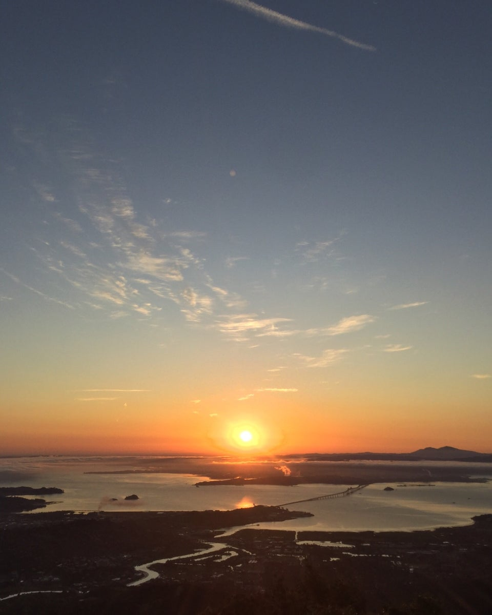 The sun rising just above East Bay hills under an orange to light blue sky as viewed from the East Peak of Mt. Tam