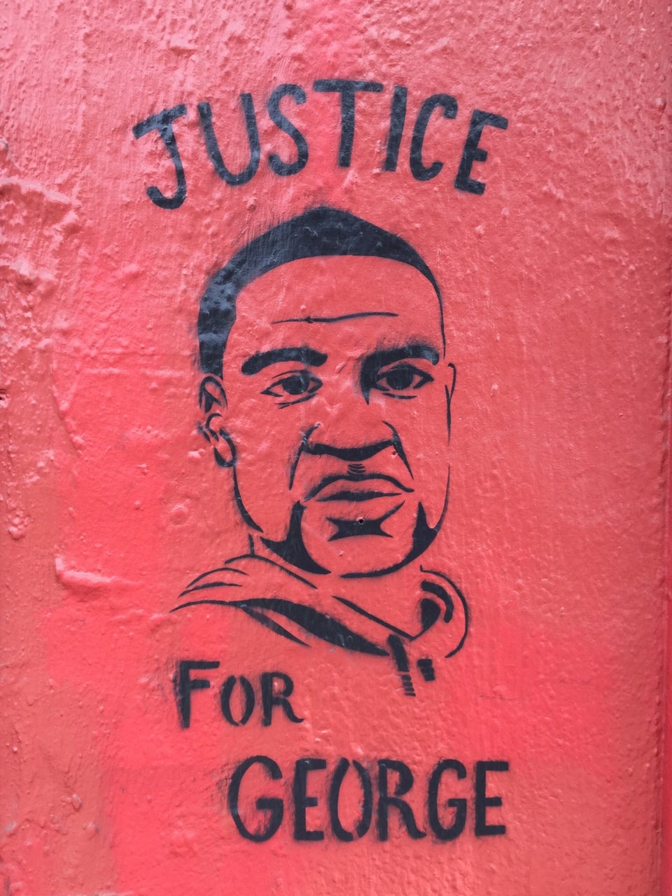 Stencil street art of George Floyd on a red wall with the word JUSTICE above his head, and FOR GEORGE below.